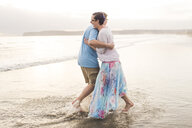 Side view of happy couple embracing while standing on shore at beach - CAVF54026
