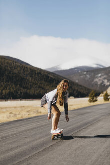 Full length of carefree young woman skateboarding on road during sunny day - CAVF54029