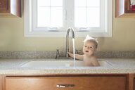 Portrait of shirtless baby boy playing with water while sitting in kitchen sink - CAVF54083