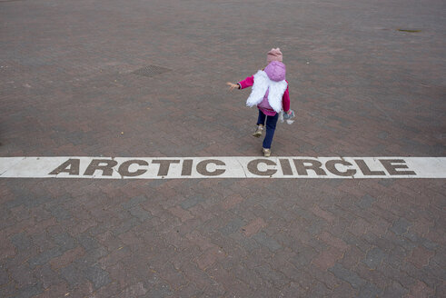 Finland, Rovaniemi, Girl Crossing the Arctic Circle - PSIF00152