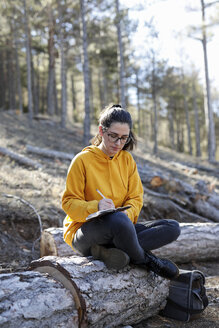 Young woman with yellow sweater in the forest, writing - GRSF00004
