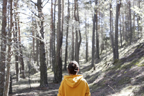 Rear view of young woman with yellow sweater in the forest - GRSF00010