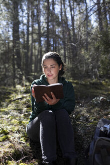 Young woman with yellow sweater in the forest, writing - GRSF00013