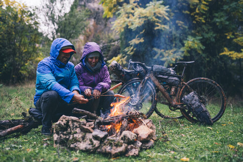 Laughing couple with with bmx bikes sitting at camp fire grilling sausages - OCMF00092