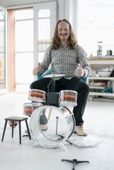 Portrait of confident man sitting at toy drums - KNSF05195
