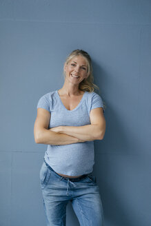 Portrait of smiling pregnant woman standing at blue wall - KNSF05228
