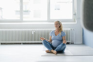 Pregnant woman sitting on the floor practicing yoga - KNSF05237