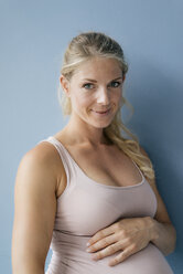 Portrait of smiling pregnant woman standing at blue wall - KNSF05264