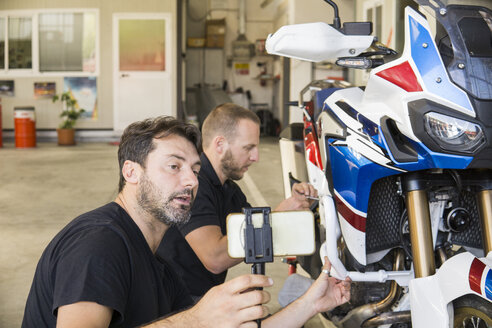 Mechanic working on motorcycle in workshop filmed by his partner - FBAF00154