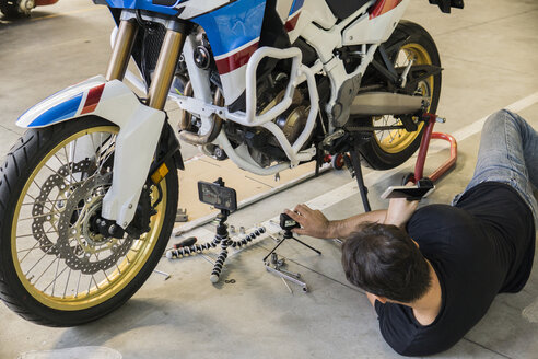 Man placing video camera next to motorcycle in workshop - FBAF00157