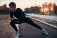 Sportive man stretching in the evening - ZEDF01729