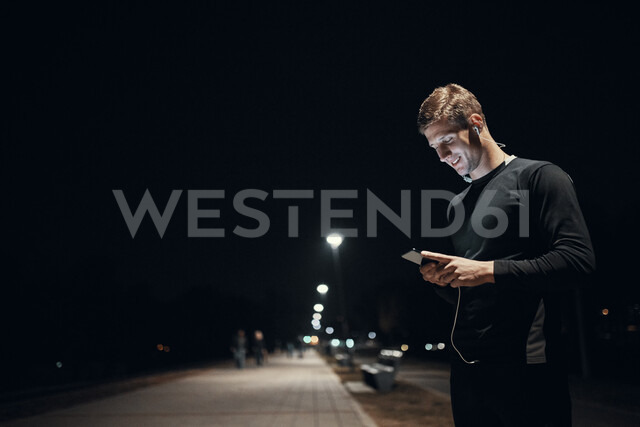Sportive young man with smartphone and earphones outdoors at night - ZEDF01738