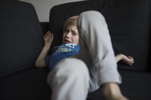 Portrait of sad boy lying on couch - JLOF00294