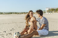 Smiling young couple sitting on the beach with a ball - KIJF02079
