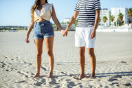 Close-up of couple holding hands on the beach - KIJF02085
