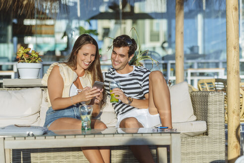 Happy young couple sitting on the terrace of a bar looking at cell phone - KIJF02088