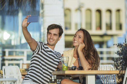 Happy young couple taking a selfie on the terrace of a bar - KIJF02091