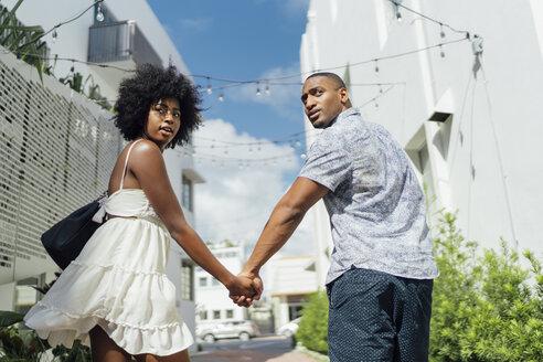USA, Florida, Miami Beach, young couple walking down the road turning round - BOYF00796