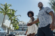 USA, Florida, Miami Beach, happy young couple crossing the street - BOYF00826
