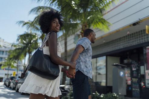 USA, Florida, Miami Beach, happy young couple crossing the street - BOYF00829