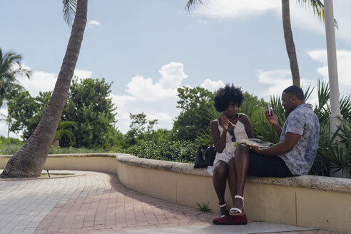 USA, Florida, Miami Beach, young man taking a picture of girlfriend eating a salad in a park - BOYF00856