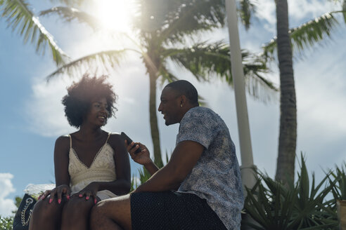 USA, Florida, Miami Beach, smiling young couple with cell phone talking in a park - BOYF00859