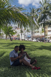USA, Florida, Miami Beach, young couple using tablet and laptop on lawn in a park - BOYF00862