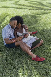 Smiling young couple sharing tablet on lawn in a park - BOYF00865