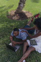Young couple using tablet and laptop on lawn in a park - BOYF00868