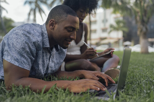 USA, Florida, Miami Beach, young couple using tablet and laptop on lawn in a park - BOYF00877