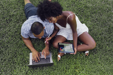 Young couple using tablet and laptop on lawn in a park - BOYF00880