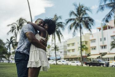 USA, Florida, Miami Beach, happy young couple hugging in a park in summer - BOYF00889