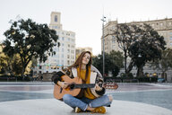 Red-haired woman playing the guitar in the city - JRFF01919