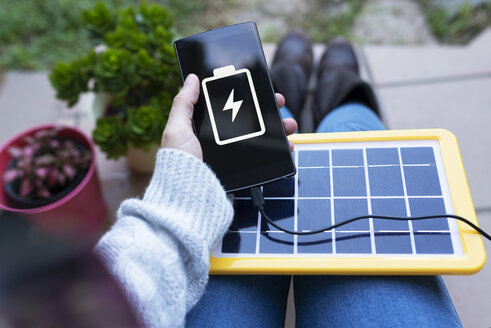 Renewable energy technology, solar panel charging a mobile phone battery - GEMF02497