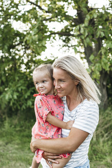 Smiling mother carrying daughter in nature - HMEF00050