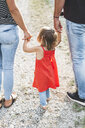 Girl walking on parent's hands on a field path - HMEF00053