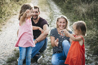Happy family with two daughters playing with confetti on a field path - HMEF00056