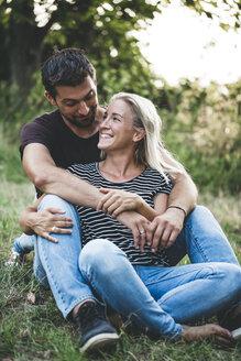 Happy couple sitting on a meadow - HMEF00062