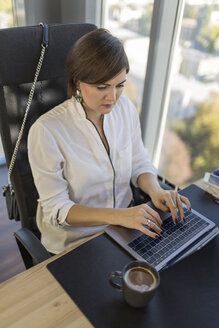 Woman using laptop at desk in office - VGF00093
