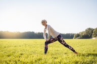 Smiling senior woman stretching on rural meadow - DIGF05431