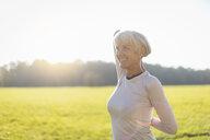 Smiling senior woman doing gymnastics on rural meadow - DIGF05434