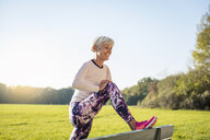 Smiling senior woman stretching on a bench in rural landscape - DIGF05437