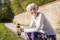 Smiling sportive senior woman holding bottle in park - DIGF05440