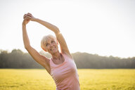 Senior woman stretching on rural meadow at sunset - DIGF05458