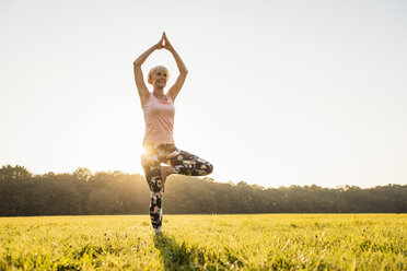Senior woman doing yoga on rural meadow at sunset - DIGF05461