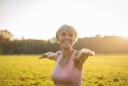 Portrait of smiling senior woman doing yoga on rural meadow at sunset - DIGF05464