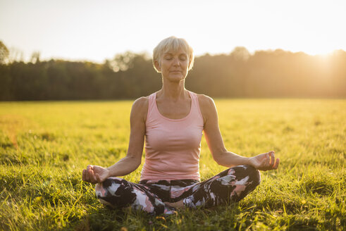 Senior woman in lotus position on rural meadow at sunset - DIGF05467
