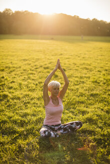 Senior woman doing yoga on rural meadow at sunset - DIGF05470