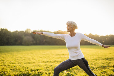 Senior woman doing yoga on rural meadow at sunset - DIGF05473