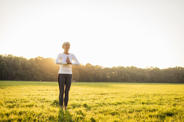 Senior woman doing yoga on rural meadow at sunset - DIGF05476